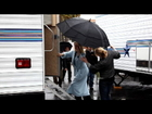 Naomi Watts keeps dry on the rainy set of