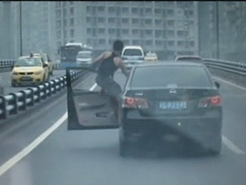 Man filmed climbing out of car whilst driving in China | PopScreen